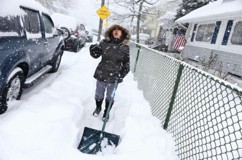 Hour photo / Erik Trautmann Norwalker Mercy Acojido braves the snowstorm to clear the sidewalks in front of her residence Thursday morning.
