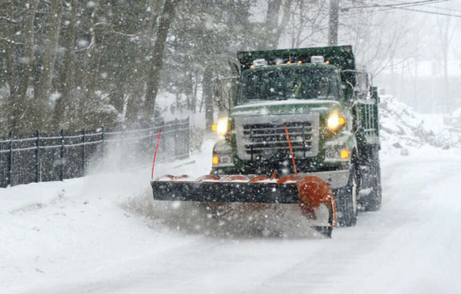Hour photo / Erik Trautmann Norwalk DPW workers clear roadways during the snowstorm Thursday morning.