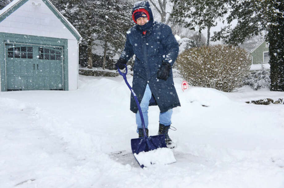 Hour photo / Erik Trautmann Norwalker David Plavin braves the snowstorm his driveway Thursday morning.