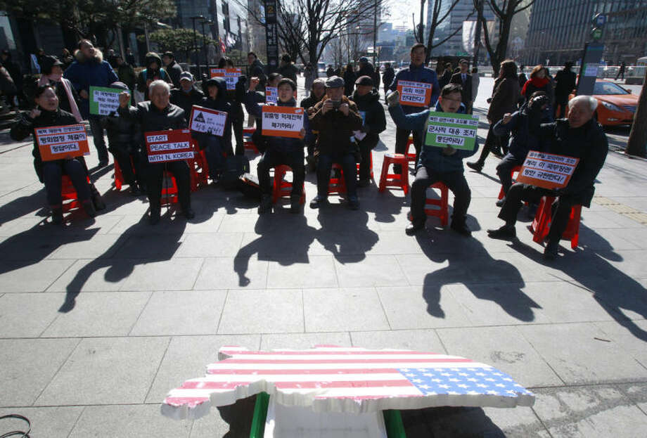 """Protesters stage a rally opposing the scheduled visit of Secretary of State John Kerry near the U.S. embassy in Seoul, South Korea, Tuesday, Feb. 11, 2014. Kerry will visit South Korea on Thursday to discuss issues of mutual concerns, including efforts to denuclearize North Korea. The letters at cards read """" Oppose South Korea and U.S. joint military exercise and scrap the South Korea-U.S. alliance"""". (AP Photo/Ahn Young-joon)"""