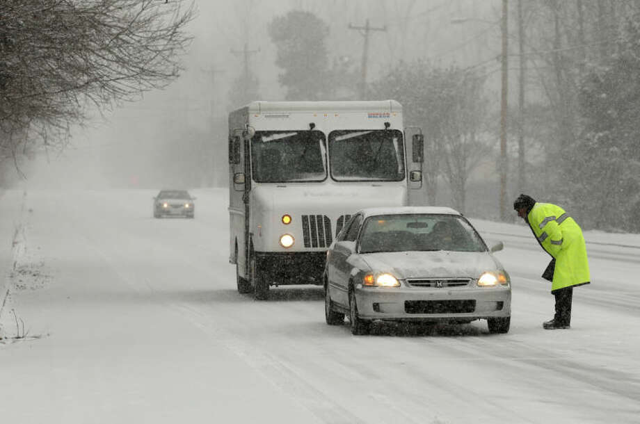 AP Photo/Chuck BurtonPolice redirect traffic as a winter storm moves into the area Wednesday in Charlotte, N.C.