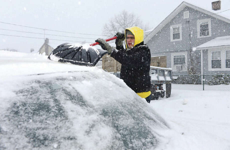 Hour photo / Erik Trautmann Norwalker and National Guard Sgt. Israel Guardado clears his car to report for duty Thursday morning.