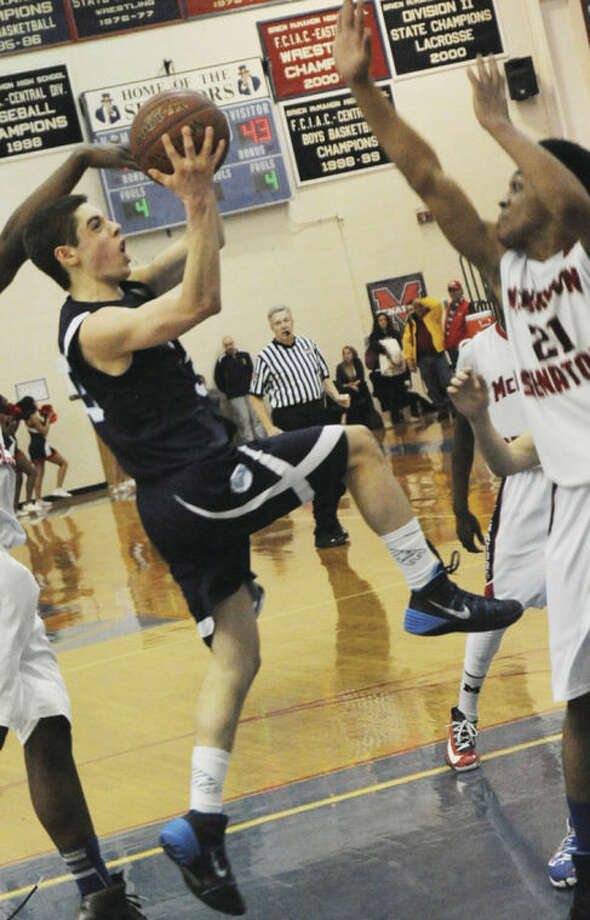 Hour photo/Matthew VinciWilton's Matt Shifrin, left, goes up for a shot over Timothy Hinton Jr. of Brien McMahon during Tuesday night's game.