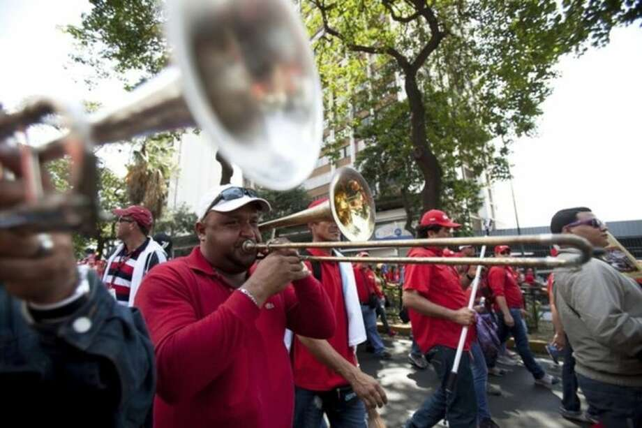 Employees of Petroleos de Venezuela, PDVSA, play music during a pro government march in Caracas, Venezuela, Tuesday, Feb. 18, 2014. The Venezuelan government accuses the Obama administration of siding with student protesters it has blamed for violence that led to three deaths last week. Maduro claims the U.S. is trying to stir up unrest to regain dominance of South America's largest oil producer.(AP Photo/Alejandro Cegarra)