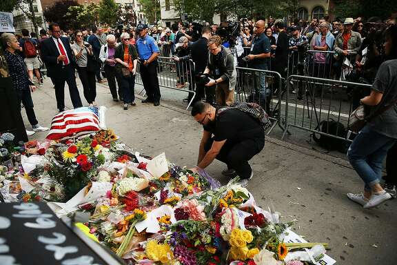 NEW YORK, NY - JUNE 13:  People pause in front of the iconic New York City gay and lesbian bar The Stonewall Inn to lay flowers and grieve for those killed in Orlando on June 13, 2016 in New York City. An American-born man who had recently pledged allegiance to ISIS killed 50 people early Sunday at a gay nightclub in Orlando, Florida. The massacre is the deadliest mass shooting in United States history.  (Photo by Spencer Platt/Getty Images)