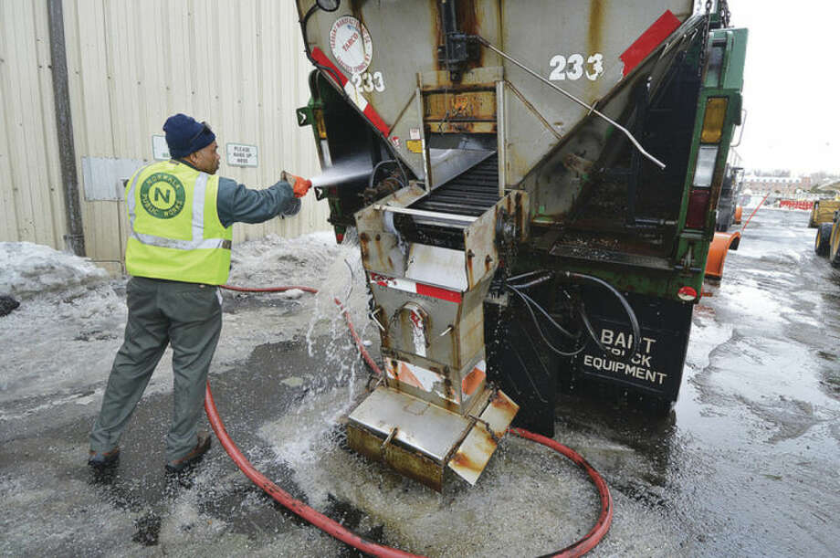 Hour Photo/Alex von Kleydorff Oliver Lawrence uses a high pressure hose to clear the salt spreader on his snow plow at the DPW garage on Wednesday.