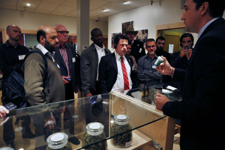 ADVANCE FOR USE SUNDAY, FEB. 16, 2014, AND THEREAFTER - FILE - In this Oct. 23, 2013, Norton Arbelaez, right, the owner of River Rock marijuana dispensary, shows his products to foreign lawmakers, Julio Bango, of Uruguay, second from left, Larry Campbell, of Canada, third from left, and Fernando Belaunzaran, of Mexico, fifth from left, during a tour of his business in Denver. Several foreign lawmakers pushing for drug law reforms at home took a close up look the evolving legal marijuana industry in Colorado. Washington and Colorado passed recreational laws in 2012 to regulate the growth and sale of taxed pot at state-licensed stores. Sales began Jan. 1 in Colorado, and are due to start later this year in Washington. Twenty states and the District of Columbia also now have medical marijuana laws. (AP Photo/Brennan Linsley, File)