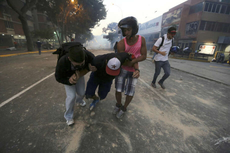 A demonstrator affected by tear gas, fired by the Bolivarian National Police, is helped after an opposition protest ended in clashes in Caracas, Venezuela, Saturday, Feb. 15, 2014. Venezuelan security forces backed by water tanks, tear gas and rubber bullets dispersed groups of anti-government demonstrators who tried to block Caracas' main highway Saturday evening. (AP Photo/Fernando Llano)