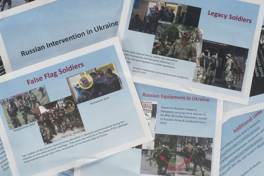 These printed copies of a presentation released by the U.S. Department of State on Thursday, April 17, 2014, purport to show Russian involvement in Eastern Ukraine. The 11-page document contains images of soldiers in eastern Ukraine that the State Department says are Russian forces, showing militants wearing similar uniforms and brandishing Russian weapons. There was no way to immediately verify the photographs, which the State Department says were taken from the Internet and social media. (AP Photo)
