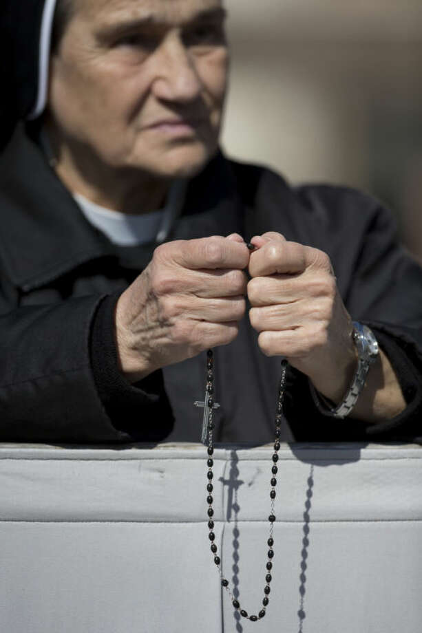 A nun holds a rosary as she prays prior to the arrival of Pope Francis to celebrate an Easter Sunday Mass in St. Peter's Square at the Vatican, Sunday, April 20, 2014. Even before Mass began, a crowd of more than 100,000 was overflowing from the cobblestoned square. Many more Romans, tourists and pilgrims were still streaming in for the pontiff's tradition Easter greeting at noon. (AP Photo/Andrew Medichini)