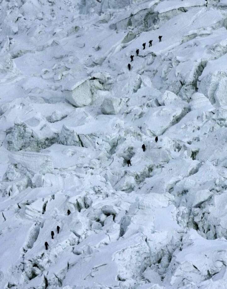 FILE - In this May 18, 2003 file photo, mountaineers pass through the treacherous Khumbu Icefall on their way to Mount Everest near Everest Base camp, Nepal. The Khumbu Icefall is a river of ice, a kilometer or so of constantly shifting glacier punctuated by deep crevasses and overhanging immensities of ice that can be as large as 10-story buildings and can move six feet in just one day. Crossing it can take 12 hours. On Friday, April 18, 2014, a piece of glacier sheared away from the mountain, setting off an avalanche of ice that killed 16 Sherpa guides as they ferried clients' equipment up the mountain. (AP Photo/Gurinder Osan, File)