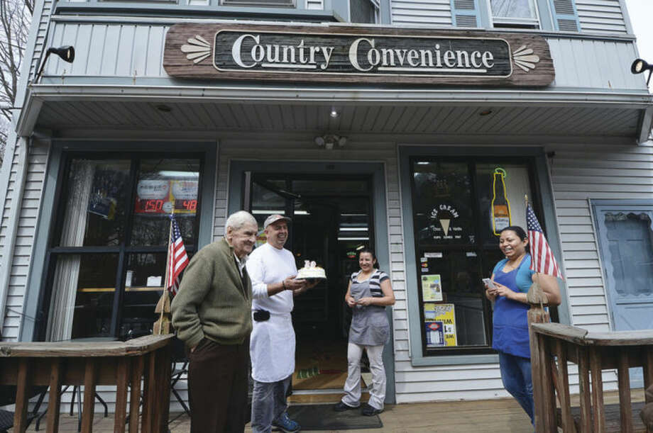 Hour Photo/Alex von Kleydorff. John Kozar celebrates 93 years with a birthday cake made and presented by Country Convenience owner Bill Varvaras.