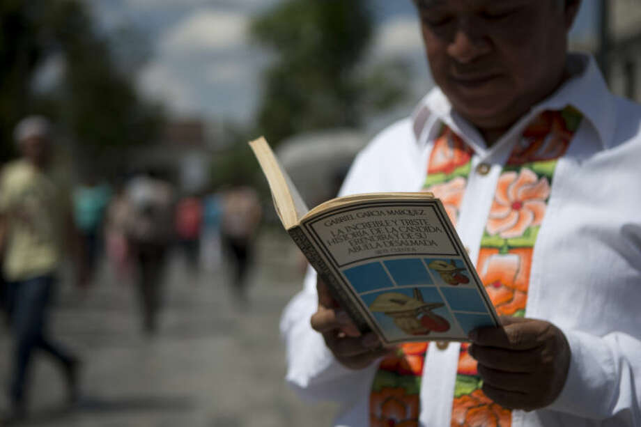 A man reads a book by Colombian Nobel Literature laureate Gabriel Garcia Marquez as he waits in line to pay his respects to the author at the Palace of Fine Arts in Mexico City, Monday, April 21, 2014. The ashes of Garcia Marquez were taken Monday to Mexico City's majestic Palace of Fine Arts, where thousands of admiring readers began paying tribute to the Colombian Nobel laureate considered one of the greatest Spanish-language authors of all time. (AP Photo/Rebecca Blackwell)