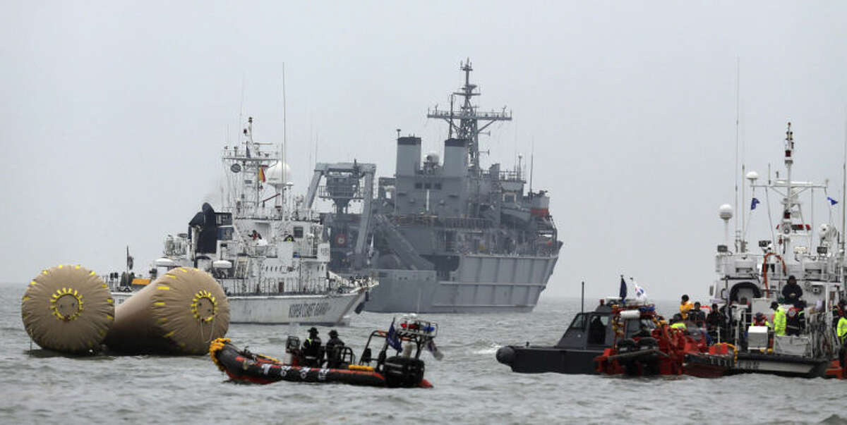 South Korean rescue team members try to search missing passengers of the sunken ferry Sewol near buoys which were installed to mark the area in the water off the southern coast near Jindo, South Korea, Saturday, April 19, 2014. The captain of the sunken South Korean ferry was arrested Saturday on suspicion of negligence and abandoning people in need, as investigators looked into whether his evacuation order came too late to save lives. Two crew members were also arrested, a prosecutor said. (AP Photo/Yonhap) Korea Out