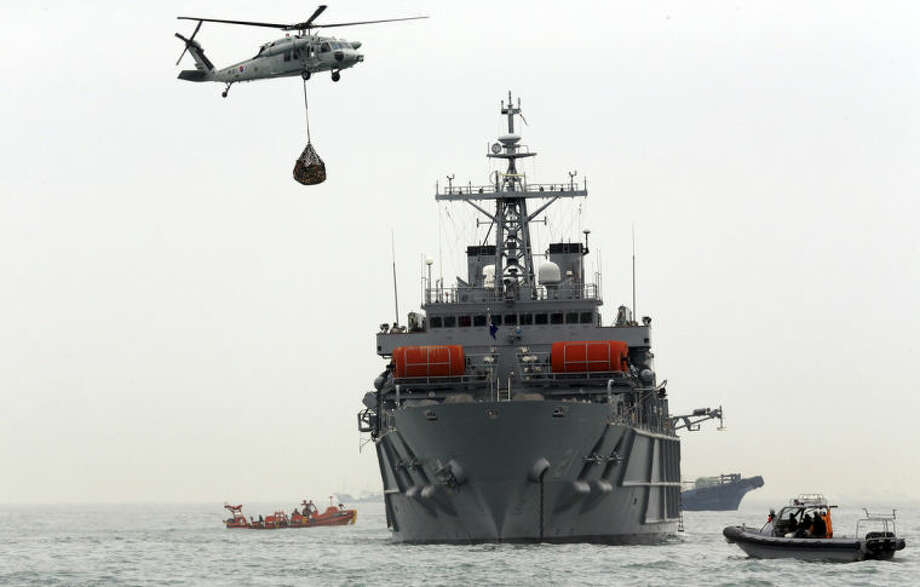 South Korean Navy and Coast Guard personnel on a ship and boats search for missing passengers aboard the sunken ferry Sewol in the water off the southern coast near Jindo, South Korea, Friday, April 18, 2014. Investigations into South Korea's ferry disaster focused on the sharp turn it took just before it started listing and on the possibility that a quicker evacuation order by the captain could have saved lives, officials said Friday, as rescuers scrambled to find some 270 people still missing and feared dead. (AP Photo/Yonhap) KOREA OUT