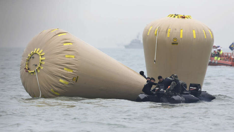South Korean navy personnel try to install buoys to mark the sunken passenger ship Sewol in the water off the southern coast near Jindo, South Korea, Friday, April 18, 2014. Rescuers scrambled to find hundreds of ferry passengers still missing Friday and feared dead, as fresh questions emerged about whether quicker action by the captain of the doomed ship could have saved lives. (AP Photo/Yonhap) KOREA OUT