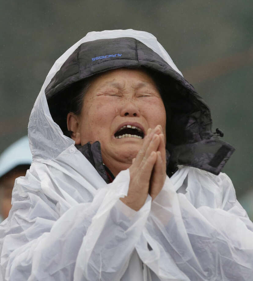 A relative of a missing passenger aboard the sunken ferry Sewol in the water off the southern coast prays while crying at a port in Jindo, south of Seoul, South Korea, Friday, April 18, 2014. Rescuers scrambled to find hundreds of ferry passengers still missing Friday and feared dead, as fresh questions emerged about whether quicker action by the captain of the doomed ship could have saved lives. (AP Photo/Lee Jin-man)