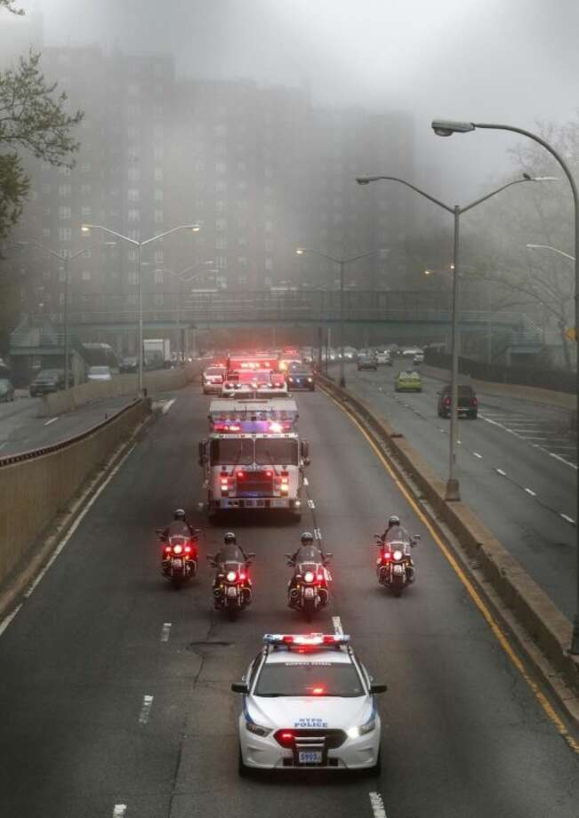 Police and fire department vehicles lead a procession along Franklin D. Roosevelt East River Drive with the unidentified remains of victims of the Sept. 11, 2001 attacks as they are returned to the World Trade Center site, Saturday, May 10, 2014, in New York. The remains were moved from the Office of the Chief Medical Examiner on Manhattan's East Side at dawn Saturday. The remains will be transferred to an underground repository in the same building as the National September 11 Memorial Museum. (AP Photo/Julio Cortez)