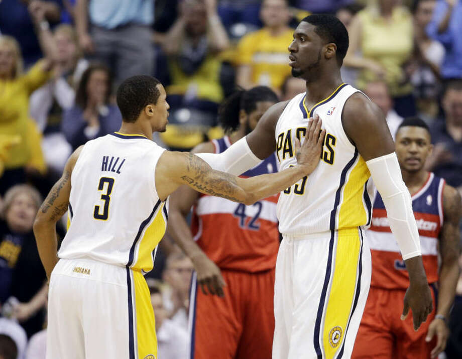 Indiana Pacers guard George Hill (3) congratulates center Roy Hibbert after he hit a bucket and was fouled by the Washington Wizards during the first half of game 2 of the Eastern Conference semifinal NBA basketball playoff series Wednesday, May 7, 2014, in Indianapolis. (AP Photo/Darron Cummings)