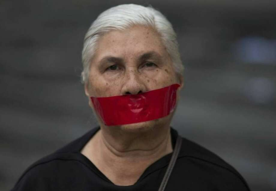 AP Photo/Fernando LlanoA woman with tape over her mouth in protest of officials breaking up protesters' camps, stands outside the United Nations headquarters in Caracas, Venezuela, Thursday, May 8. Hundreds of security forces broke up four camps maintained by student protesters, arresting 243 people in a Thursday pre-dawn raid. The camps consisting of small tents were installed more than a month ago in front of the UN building and other anti-government strongholds in the capital to protest against President Nicolas Maduro's government.