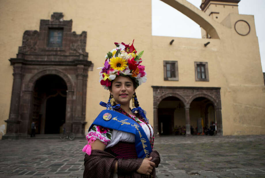 """Valeria Berenice Cabello, 18, winner of the 2014 """"Most Beautiful Flower in the Common"""" pageant, wears her ceremonial garb outside San Bernardino de Siena church, during a festival celebrating a 400-year-old representation of the Baby Jesus, in Xochimilco on the southern edge of Mexico City, Wednesday, May 7, 2014. Girls from 12 of Mexico City's 16 boroughs take part in the annual """"Most Beautiful Flower in the Common"""" competition, which has been held for more than 200 years. The popular tourist destination of Xochimilco was declared a UNESCO world heritage site in 1987. (AP Photo/Rebecca Blackwell)"""