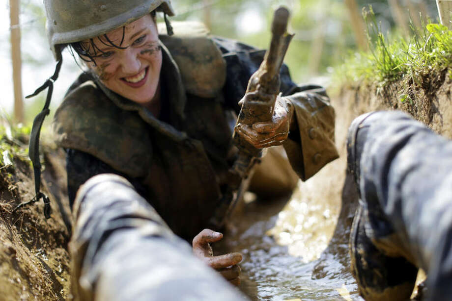 """A freshman midshipman, known as a """"plebe,"""" crawls through a muddy trench underneath barbed wire during Sea Trials, a day of physical and mental challenges that caps off the freshman year at the U.S. Naval Academy in Annapolis, Md., Tuesday, May 13, 2014. (AP Photo/Patrick Semansky)"""