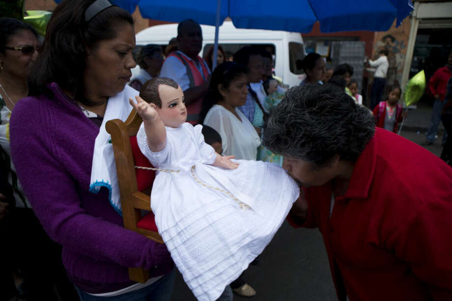 A woman kisses the costume of one of several dolls representing the Baby Jesus, during during a festival celebrating a 400-year-old representation of the Baby Jesus, in Xochimilco, on the southern edge of Mexico City, Wednesday, May 7, 2014. In Xochimilco, busy markets stand side by side with colonial churches, and children ride to school in boats pushed by poles, along a network of canals and floating gardens that date to pre-hispanic times. The popular tourist destination was declared a UNESCO world heritage site in 1987. (AP Photo/Rebecca Blackwell)