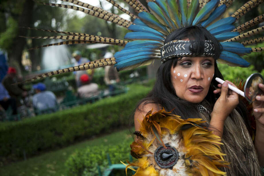 Street performer Judit Pozos puts the finishing touches on her Aztec costume, as she and her partner prepare to perform blessings with incense and a conch shell, in the central square in Xochimilco, on the southern edge of Mexico City, Wednesday, May 7, 2014. In Xochimilco, busy markets stand side by side with colonial churches, and children ride to school in boats pushed by poles, along a network of canals and floating gardens that date to pre-hispanic times. The popular tourist destination was declared a UNESCO world heritage site in 1987. (AP Photo/Rebecca Blackwell)