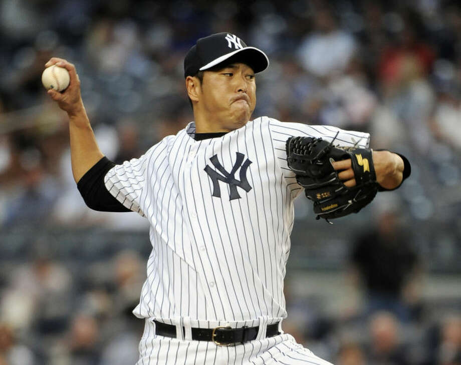 New York Yankees starting pitcher Hiroki Kuroda winds up a pitch against the New York Mets in the first inning of an interleague baseball game at Yankee Stadium on Monday, May 12, 2014, in New York. (AP Photo/Kathy Kmonicek)