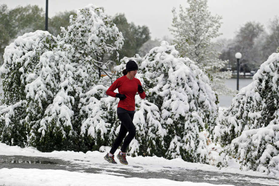 Heavy snow weighs down trees and bushes as a woman runs in Washington Park in Denver on Monday, May 12, 2014. A spring storm that has brought over a foot of snow to parts of Colorado, Wyoming and Nebraska and thunderstorms and tornadoes to the Midwest was slowing down travelers and left some without power Monday morning. (AP Photo/Ed Andrieski)