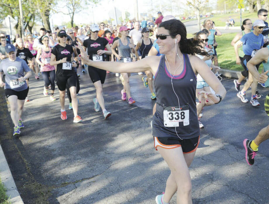 Jennifer Walker waves to her family, husband Joseph and daughters Sofia and Isabelle Sunday at the annual Mothers Day 10 K race at Calf Pasture Beach. Hour photo/Matthew Vinci