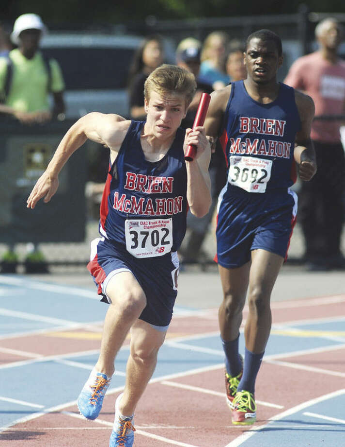 Hour photo/John NashBrien McMahon's Niko Petridis, left, races away from teammate Justin Frederick during the final leg of the 4x100 relay in Tuesdays CIAC Class LL championship meet in Danbury.