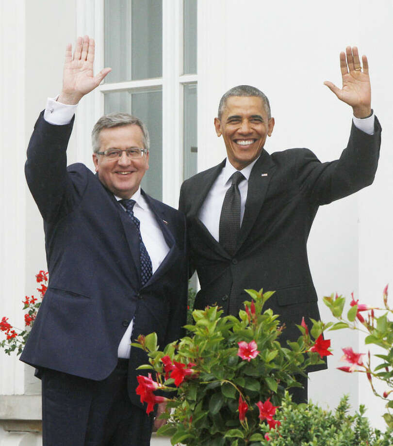 U.S. President Barack Obama,right, and Poland's President Bronislaw Komorowski ,left, wave at Belveder residence in Warsaw, Poland, on Tuesday June 3, 2014.Obama came to Poland to meet regional leaders and attend ceremonies marking 25 years of Poland's democracy. (AP Photo/Czarek Sokolowski)