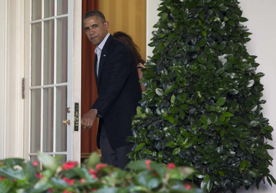 President Barack Obama opens the door of the Oval Office to go to a news conference in the Rose Garden of the White House in Washington on Saturday, May 31, 2014 with Jani Bergdahl and Bob Bergdahl about the release of their son, U.S. Army Sgt. Bowe Bergdahl. Bergdahl, 28, had been held prisoner by the Taliban since June 30, 2009. He was handed over to U.S. special forces by the Taliban in exchange for the release of five Afghan detainees held by the United States. (AP Photo/Carolyn Kaster)