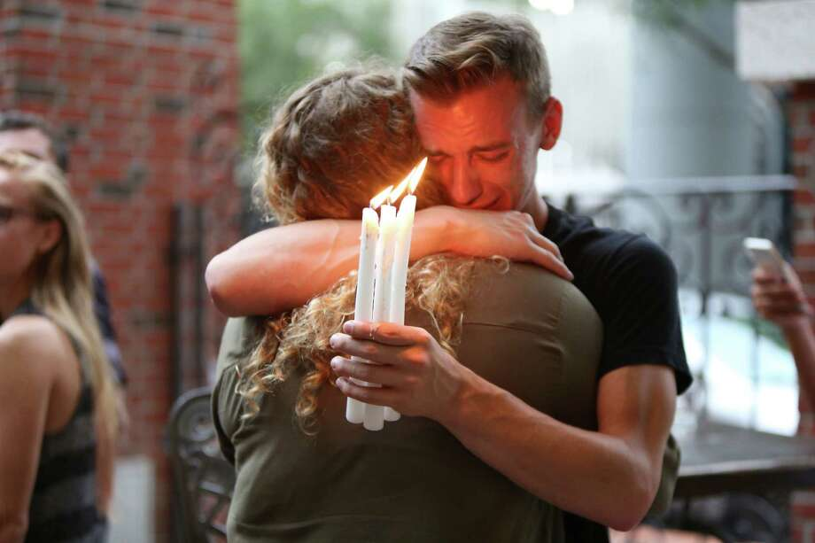 Brett Morian, from Daytona Beach, hugs an attendee during the candlelight vigil at Ember in Orlando, Fla., on Sunday, June 12, 2016. (Joshua Lim/Orlando Sentinel/TNS) Photo: Joshua Lim, MBR / Orlando Sentinel