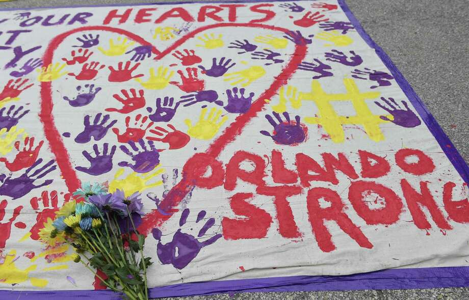 """A makeshift memorial with flowers and hand prints is seen in a parking lot near the Pulse nightclub in Orlando, Florida on June 12, 2016. A somber President Barack Obama  expressed grief and outrage at the """"horrific massacre"""" of 50 late-night revelers at an Orlando gay club, branding it an act of terror and hate. / AFP PHOTO / Mandel NGANMANDEL NGAN/AFP/Getty Images Photo: MANDEL NGAN, Staff / AFP or licensors"""