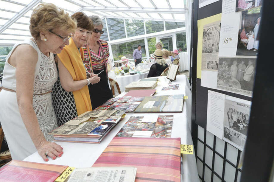 Hour Photo/Alex von Kleydorff Members look over 90 years of news on the Past and Present display at The Norwalk Garden Club's 90 year anniversary high tea at The Norwalk Inn