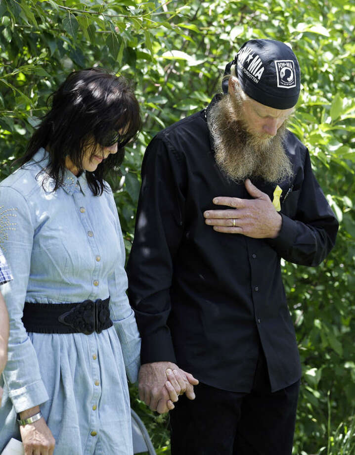 FILE - In this Saturday, June 22, 2013 file photo, Bob Bergdahl, right, and Jani Bergdahl, the parents of captive U.S. Army Sgt. Bowe Bergdahl, hold hands as they pray at the