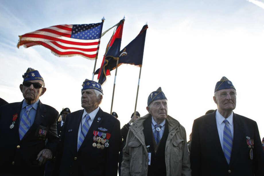 From left, World War II veterans of the U.S. 29th Infantry Division, Hal Baumgarter, 90 from Pennsylvania, Steve Melnikoff, 94, from Rhode Island, Don McCarthy, 90 from Maryland, and Morley Piper, 90, from Massachusetts, attend a D-Day commemoration, on Omaha Beach, western France , Friday June 6, 2014. Veterans and Normandy residents are paying tribute to the thousands who gave their lives in the D-Day invasion of Nazi-occupied France 70 years ago. World leaders and dignitaries including President Barack Obama and Queen Elizabeth II will gather to honor the more than 150,000 American, British, Canadian and other Allied D-Day troops who risked and gave their lives to defeat Adolf Hitler's Third Reich. (AP Photo/Thibault Camus)