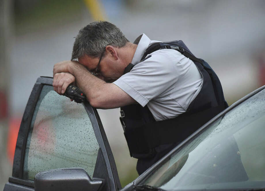 A Royal Canadian Mounted Police officer rests his head at a roadblock in Moncton, New Brunswick, on Thursday, June 5, 2014. RCMP officers combed the streets and woods of this normally tranquil city Thursday in search of a man suspected of killing three officers in the deadliest attack on their ranks in nearly a decade. The suspect, 24-year-old Justin Bourque, was armed with high-powered long firearms. He was spotted three times while eluding the massive manhunt that emptied roads and kept families hunkered in their homes in Moncton, an east coast city where gun violence is rare. (AP Photo/The Canadian Press, Andrew Vaughan)