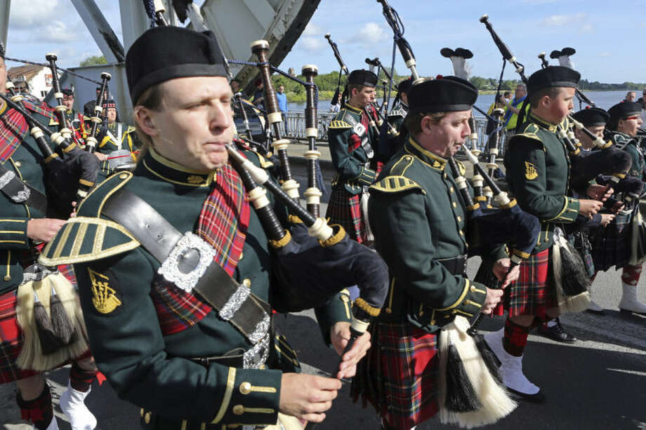 A Scottish pipe band parades on Pegasus Bridge in Benouville western France, Thursday June 5, 2014, as part of the commemoration of the 70th anniversary of the D Day. World leaders and veterans prepare to mark the 70th anniversary of the invasion this week in Normandy. (AP Photo/Remy de la Mauviniere)