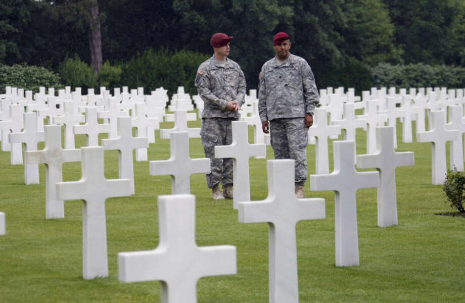 LTC Patrick Wilkins, right, 42, and Sergeant Major Stephen Yarberry of 173rd Airborne Brigade, walk in the Normandy American Cemetery and Memorial, in Colleville sur Mer, France, Wednesday June 4, 2014. World leaders and veterans prepare to mark the 70th anniversary of the invasion this week in Normandy. (AP Photo/Claude Paris)