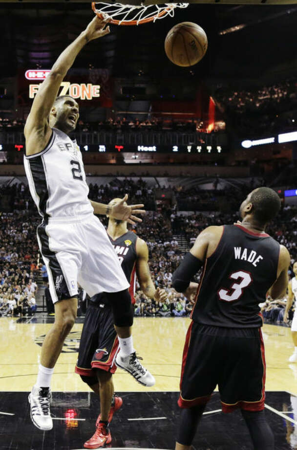 San Antonio Spurs forward Tim Duncan dunks as Miami Heat guard Dwyane Wade (3) looks on during the first half in Game 2 of the NBA basketball finals on Sunday, June 8, 2014, in San Antonio. (AP Photo/Eric Gay)