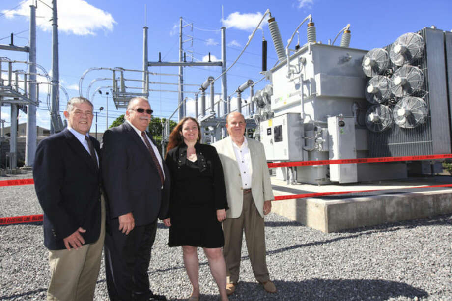Hour Photo / Chris Palermo. Third Taxing District Comissioner David Brown, Comission Chairman Charlie Yost, Comissioner Debora Goldstein and Treasurer Dr. Michael Intrieri pose in front of the Fitch Street substation during dedication ceremony Friday morning.