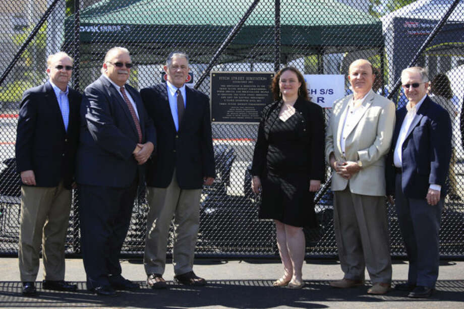 Hour Photo / Chris Palermo. Third Taxing District General Manager Jim Smith, Commision Chairman Charlie Yost, Commissioner David Brown, Comissioner Debora Goldstien, Treasurer Dr. Michael Intrieri and Assistant General Manager Ron Scofield pose in front of the Fitch Street substation plaque during the substation dedication Friday morning.