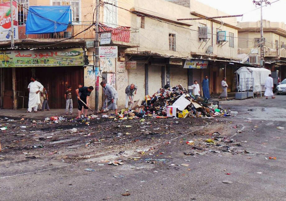 People clean up a street in the northern city of Mosul, Iraq, Friday, June 13, 2014. Iraqi officials say al-Qaida-inspired militants who this week seized much of the country's Sunni heartland have pushed into an ethnically mixed province northeast of Baghdad, capturing two towns there.(AP Photo)