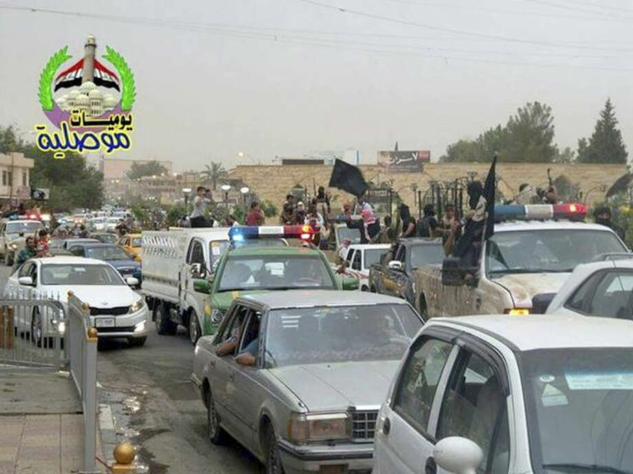 In this still image posted on a militant Twitter account on Wednesday, June 11, 2014, which has been authenticated based on its contents and other AP reporting, militants wave the black flag used by the al-Qaida-inspired Islamic State of Iraq and the Levant (ISIL) as they parade down a main road in Mosul, Iraq in captured Iraqi Army and Police vehicles. Iraqi officials say al-Qaida-inspired militants who this week seized much of the country's Sunni heartland have pushed into an ethnically mixed province northeast of Baghdad, capturing two towns there.(AP Photo/militant source via Twitter)