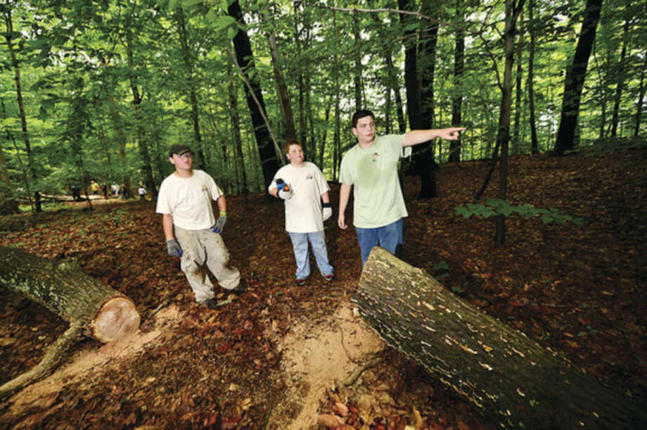 Hour photo / Erik TrautmannBoy Scout Bradley Carrano from Troop 2 directs crews of boy scouts and parents including scouts Tommy Carrano and Michael Mercado who work on improving the hiking trails at Oak Hills Park as part of Carrano's Eagle Scout project.