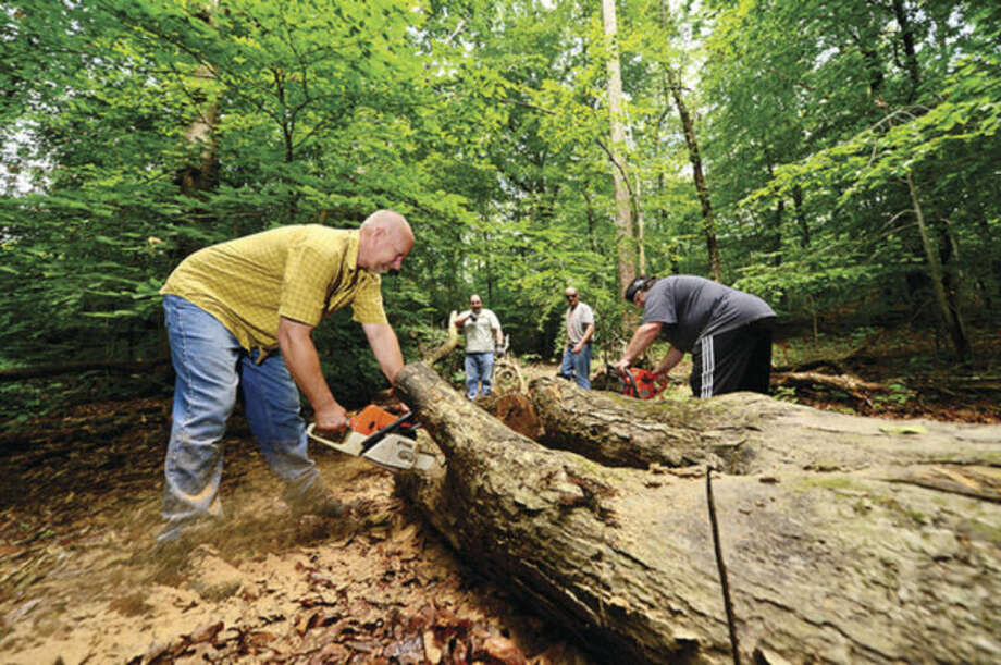 Hour photo / Erik TrautmannBoy Scout Bradley Carrano from Troop 2 directs crews of boy scouts and parents including parent Rob Griffith who work on improving the hiking trails at Oak Hills Park as part of Carrano's Eagle Scout project.