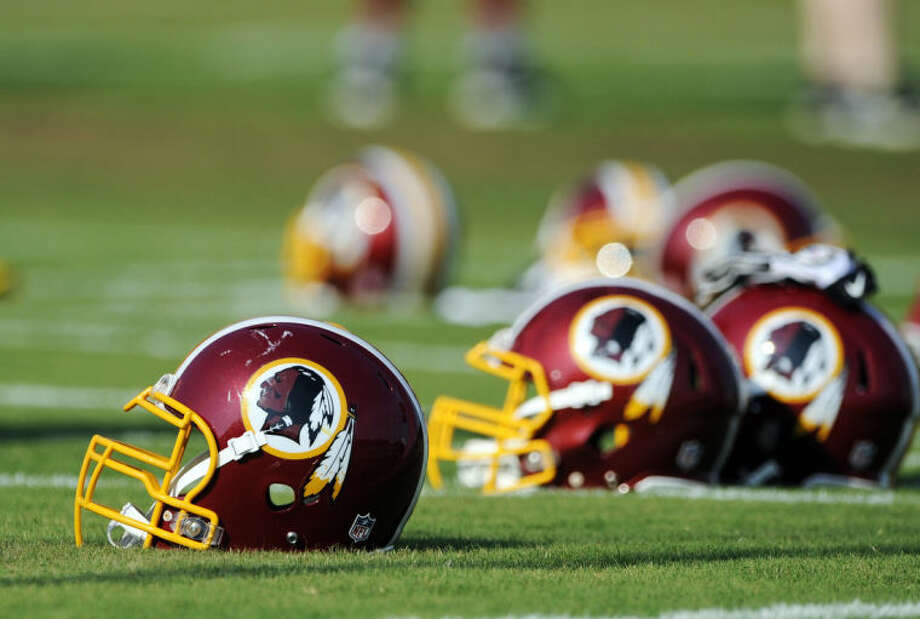 FILE - In this June 17, 2014, file photo, Washington Redskins helmets sit on the field during an NFL football minicamp in Ashburn, Va. The U.S. Patent Office ruled Wednesday, June 18, 2014, that the Washington Redskins nickname is